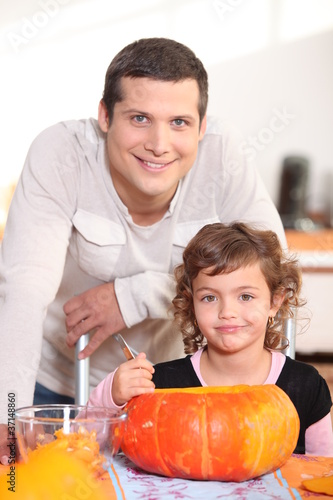 Father and daughter carving pumpkins