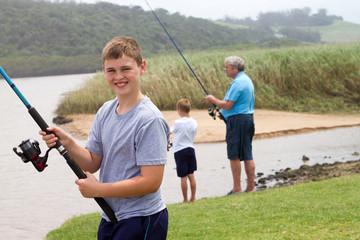 teenage boy fishing with grandpa and brother