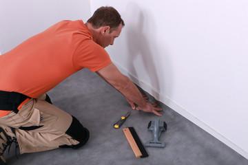 man installing linoleum