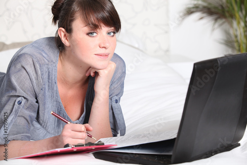 Young woman working at a laptop at home