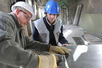 Zinc worker and apprentice in workshop