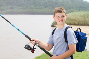 young teenage boy fishing by the lake