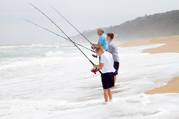 grandpa and grandsons fishing on beach