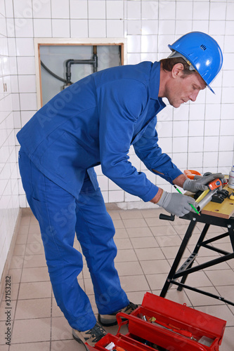 Plumber measuring plastic pipe