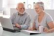 Senior people using laptop smiling