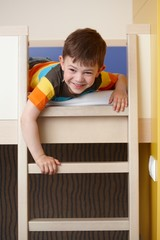 Little boy having fun on bunk bed laughing
