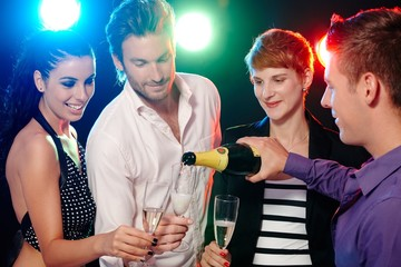 Young friends drinking champagne in disco bar