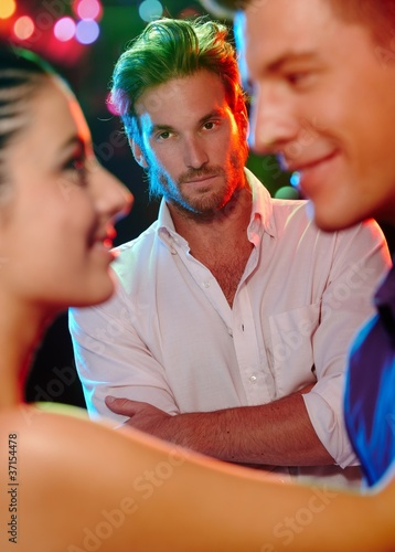 Jealous man looking at dancing couple