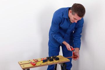Laborer cutting a copper pipe