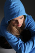 Sad teenager girl alone on floor in blue hoodie