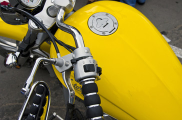 Motorcycle wheel and yellow petrol tank details.