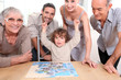 Family gathered around jigsaw puzzle