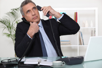 Businessman answering ringing telephones