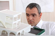 real estate businessman holding an architectural model