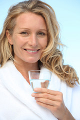 Woman drinking a glass of water in a bathrobe