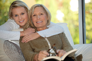 Girl with her grandmother reading a book