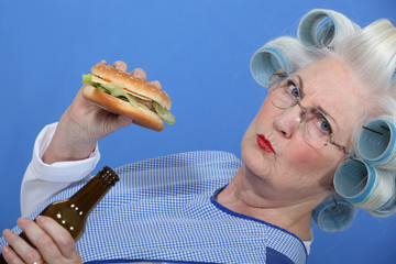 An old lady enjoying a burger and a beer.