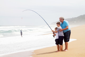 grandpa and two grandsons together fishing on beach
