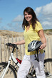 Young woman with bike at the beach
