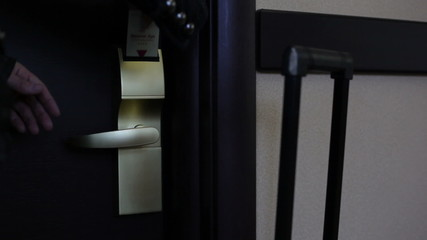 Woman opens a hotel door with a card key