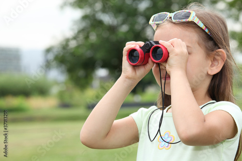 little girl watching through binoculars