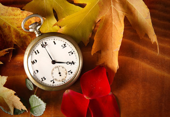 Orologio antico su tavola con foglie secche