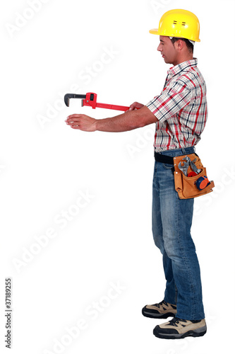 Tradesman using a pipe wrench to help drag and place an object