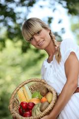 blonde woman showing a fruits basket