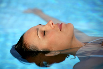 Woman relaxing in a swimming-pool