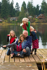 A happy gray haired Grandpa with 4 Grandchildren on a lake