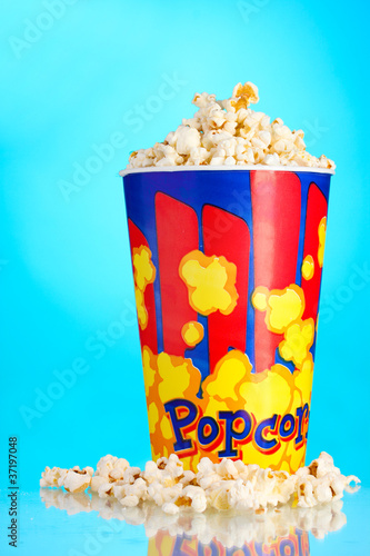 Full bucket of popcorn  on blue