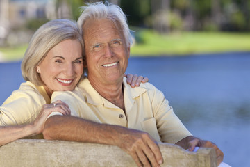 Happy Smiling Senior Couple Sitting On Park Bench Embracing