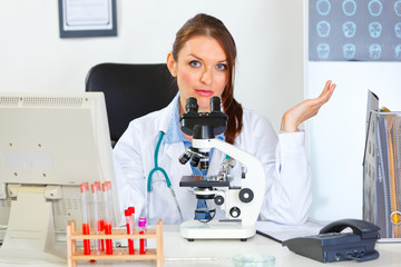 Confused doctor woman working with microscope in laboratory