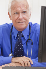 Senior Male Doctor With Stethoscope at Desk & Computer