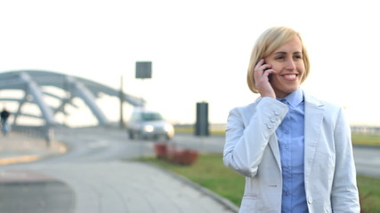 Attractive businesswoman talking on cellphone by the city street