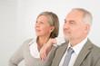 Senior businesspeople lean over shoulder colleague
