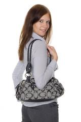 Junge Frau mit Tasche dreht sich um