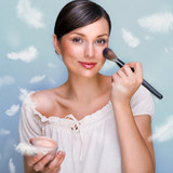 Portrait of a Beautiful woman applying makeup with brush on her