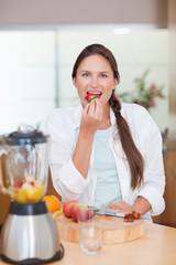 Portrait of a woman eating a strawberry