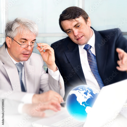 Portrait of group of businessmen at the computer. Office backgro