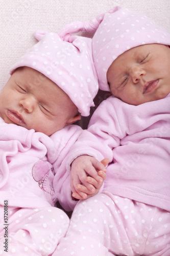 eineiige Zwillinge - Schwestern schlafen Hand in Hand