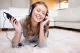 Fototapety Woman lying on the carpet enjoying music