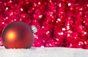 red christmas ornament in a pile of snow