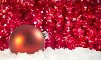 red christmas ornament in a pile of snow - ice