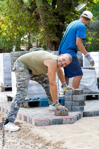 poster of man at work paving stones