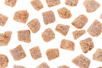 Many brown lump cane sugar cubes isolated on white, food backgro
