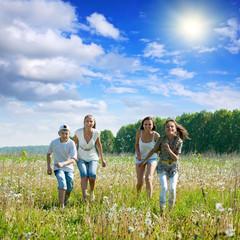 Friends running in meadow