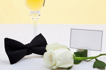 White rose, bow tie and blank place card.