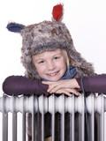 Sweet little girl with pelt cap and radiator enjoys wintertime poster