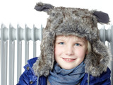 Sweet little girl with pelt cap in front of a radiator poster